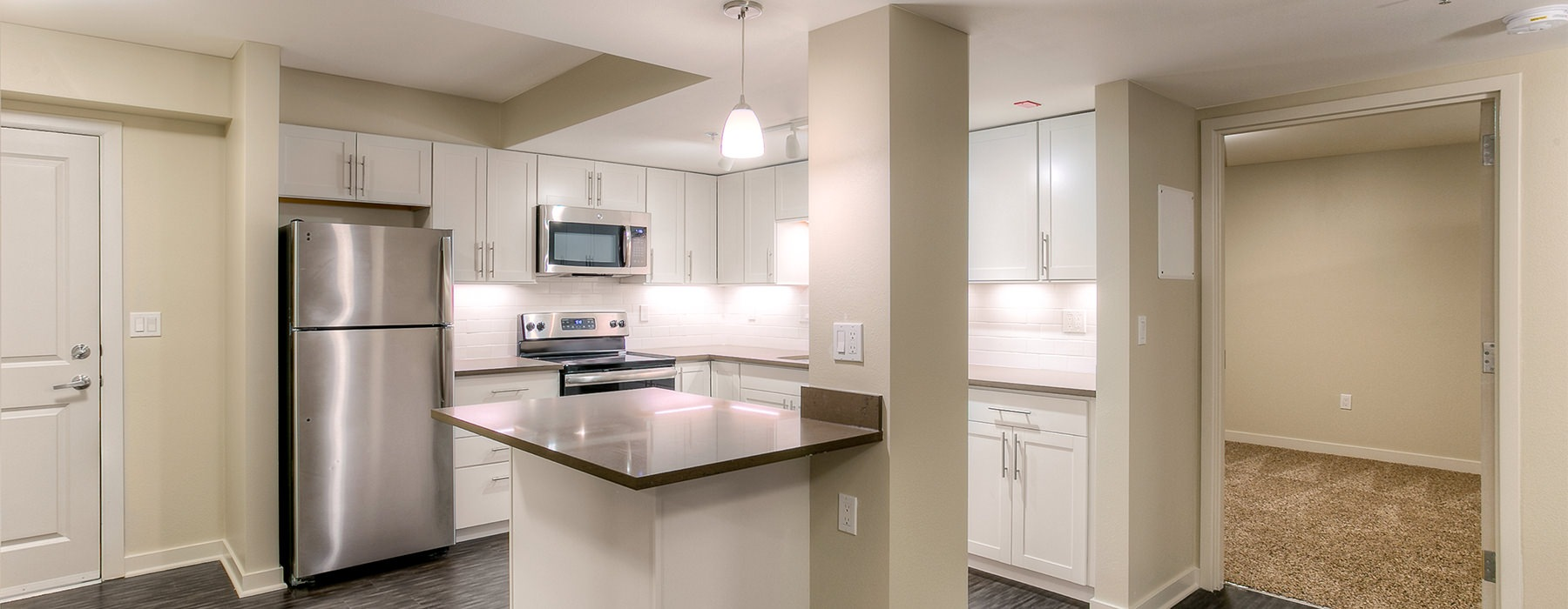 Well lit kitchen with stainless steel appliances